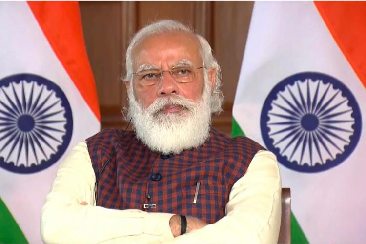 Prime Minister Narendra Modi looking into the camera with his arms crossed