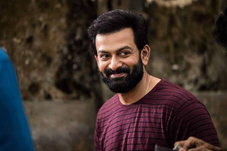Prithviraj in purple T shirt and smiling