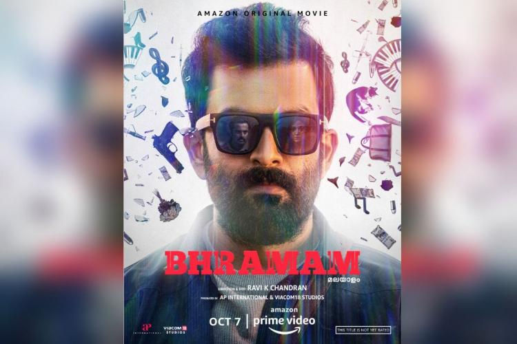 Prithviraj wearing sunglasses and a beard is in the poster of a Malayalam film Bramam against a white background with various objects flying