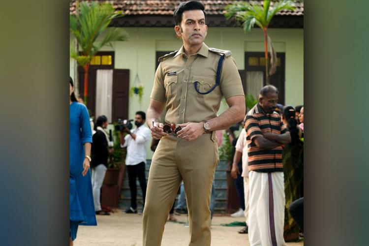 Prithvi in police uniform stands looking away as a bunch of people are in the background