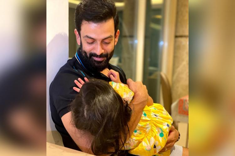 Prithviraj holds his daughter Ally who is wearing a yellow dress