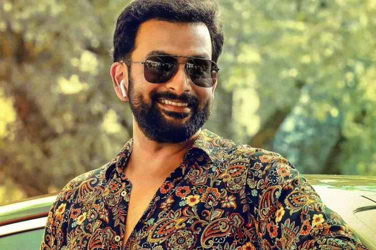 Prithviraj wearing sun shades and a fancy shirt smiles He has a beard too