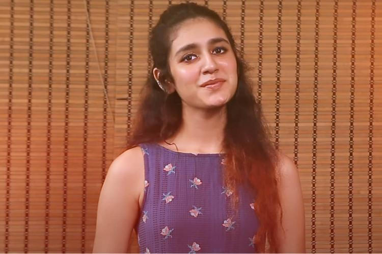 Actor Priya Prakash Varrier in a still from the official teaser of the song She is wearing a purple sleeveless outfit and standing against a brown background