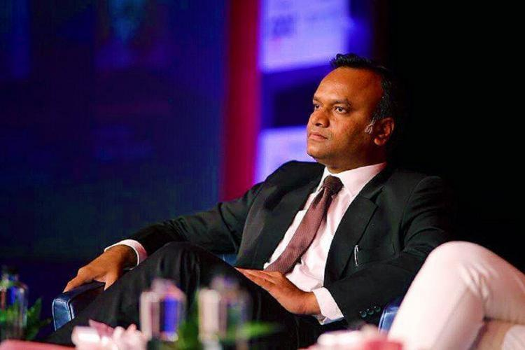 Picture of Congress leader Priyank Kharge sitting on a stage at a meeting. He is leaning back and wears a three piece suit and tie.