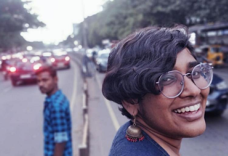 Priyanka Ulaganathan smiles from a median in the middle of traffic