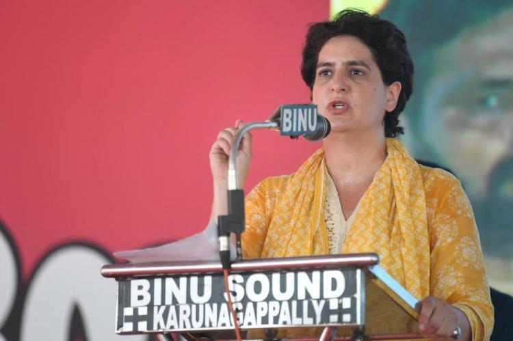 Priyanka Gandhi in a yellow salwar speaking to a crowd in Kerala