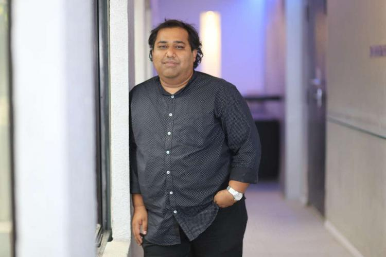 Producer CV Kumar in black shirt stands with his hand inside pocket in a well lit corridor