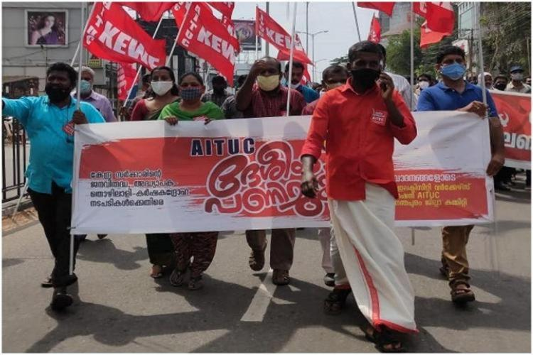 Pro Left Union workers taking out a march holding red flags in Kerala