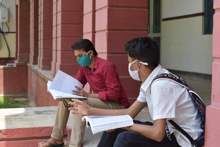 Two young men wearing masks and reading books outside an exam centre