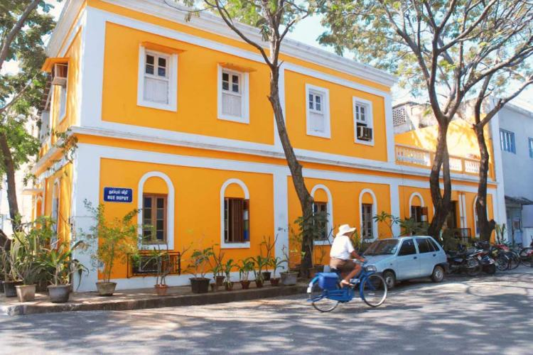 A yellow building with white windows in Puducherry and a man in a white shirt and hat cycling on the street outside it