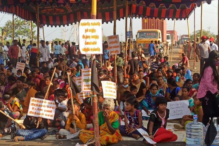 Villagers of Kattupalli Kuppam hold placards demanding permanent jobs
