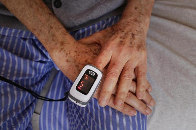 A man has a pulse oximeter on his finger as his hands are placed on his thigh
