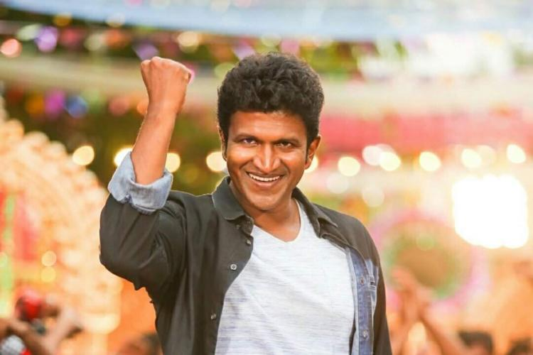 In a scene from a movie, actor Puneeth Rajkumar is seen smiling directly at the camera with one arm lifted. He is wearing a grey shirt over a white t-shirt.