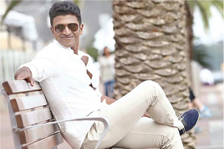 Puneeth Rajkumar sitting on a bench in a white shirt and white pants