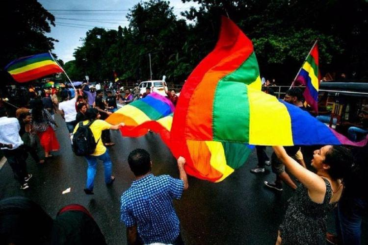 A number of people wave the queer rainbow flag and walk on a road on a rainy evening