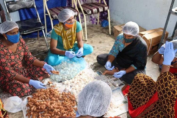 Five transwomen are seen busy engaging in making ginger garlic paste and pickles while wearing head coverings masks and gloves