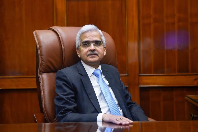 Reserve Bank of India RBI Governor Shaktikanta Das wearing a dark gray blazer with a blue tie placing his hand on a table and looking into the camera
