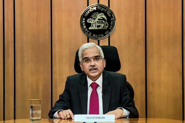 RBI Governor Shaktikanta Das giving his speech sitting in front of the RBI logo