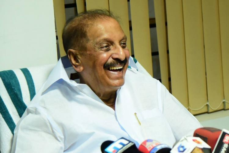 Kerala Congress leader R Balakrishna Pillai laughing while addressing media with media mikes put in front of him