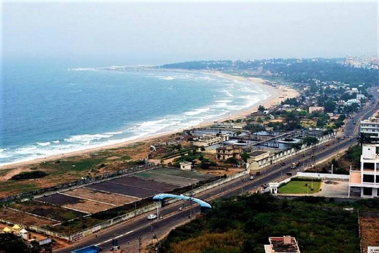 A wide view of the RK Beach in Visakhapatnam with buuidings and the road and the curving coastline