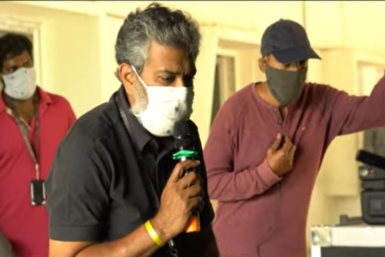 RRR shooting resumes in which S S Rajamouli can be seen wearing a black shirt holding a mike along with two others