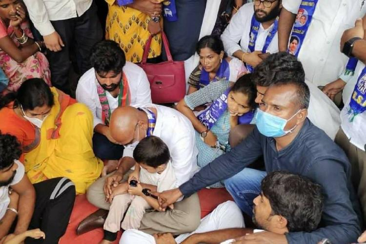 Praveen Kumar, bald and wearing a white shirt has a child on his lap while a number of people are sitting and standing around him