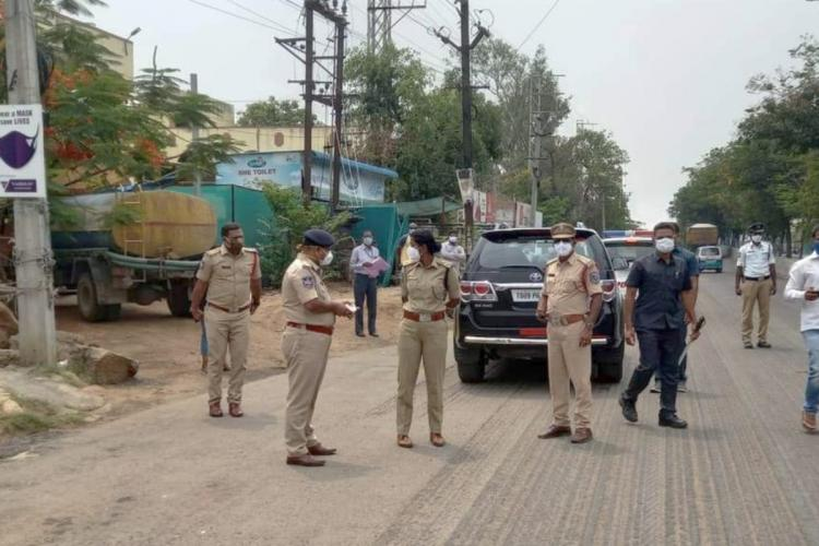 A senior police officer interacts with officials during curfew imposition in Rachakonda Police Commissionarate limits