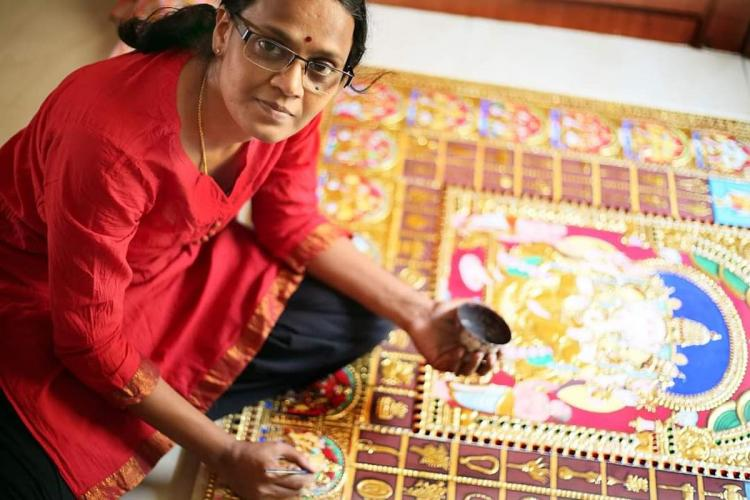 Radha Prabhu a Thanjavur painting artist working on a big canvas