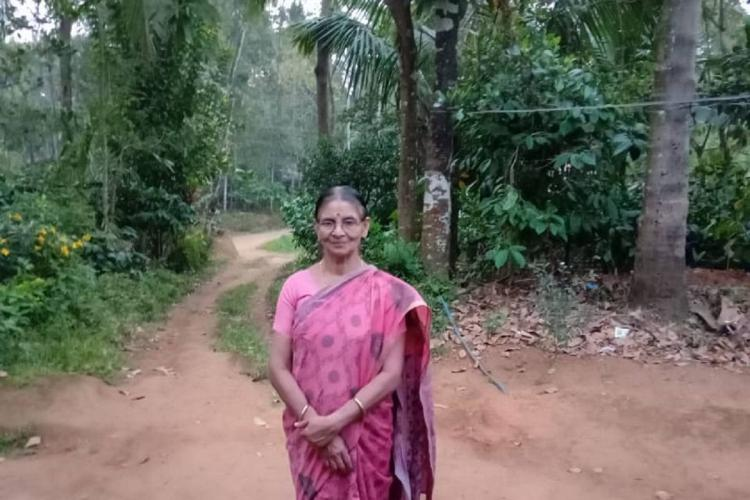 Radhamani in a purple sari stands in a rural area with trees in the background and a muddy path