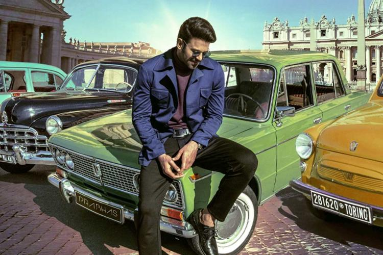 Prabhas lcan be seen in a blue jacket with goggles He can be seen sitting on a green coloured vintage car with Prabhas on the nameplate