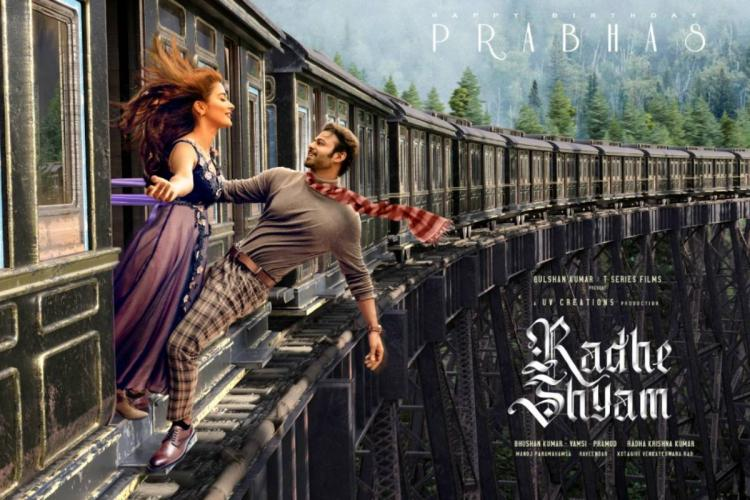 Still from Radhe Shyam where a train is shown curving on the rails as Pooja Hegde and Prabhas hang out of a door in the foreground there are green mountains in the background