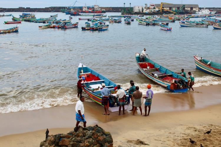 Fisherfolk near fishing boats preparing to venture into the sea
