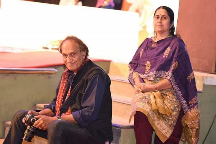Raghu Rai in black seated with his camera while Lekshmy in her salwar sits on steps above him