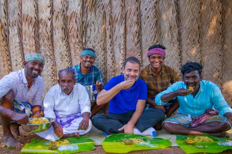 Rahul Gandhi relishing mushroom biryani with TN villagers in cooking channel He is wearing a blue t-shirt and jeans