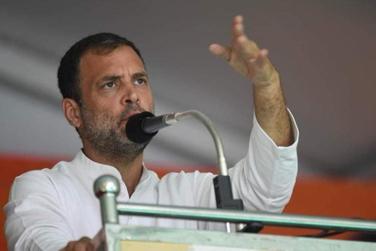 Rahul Gandhi dressed in a white kurta gestures while addressing a rally