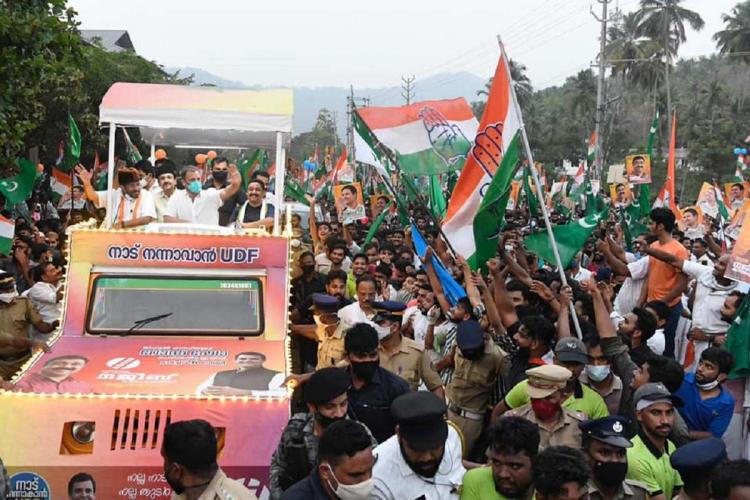 Rahul Gandhi in a pink vehicle waves to a massive crowd outside holding Congress flags during a roadshow