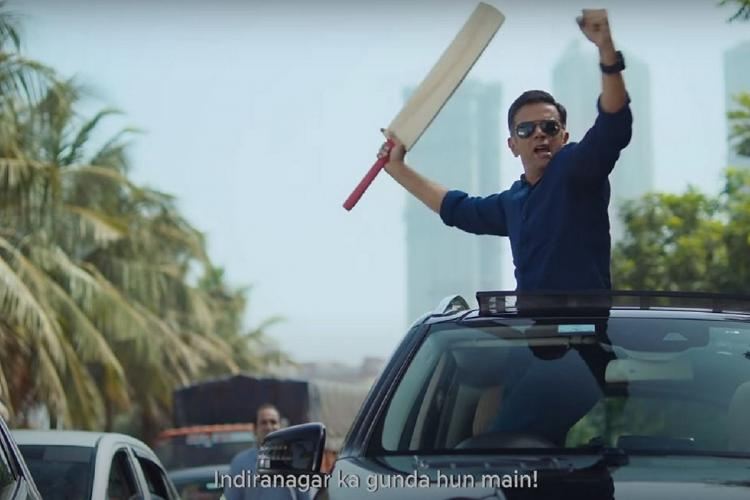 Rahul Dravid in a blue shirt and shades standing up in the sunroof of a car with both hands raised in the air and a cricket bat in his right hand