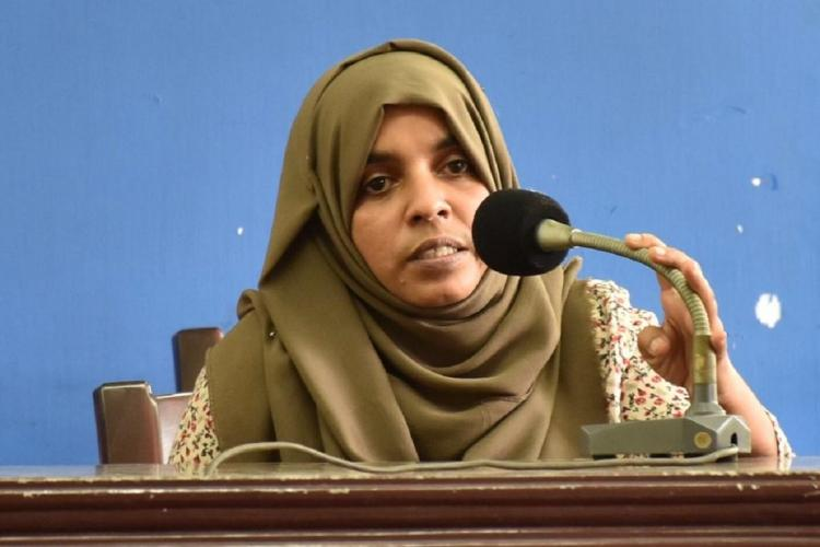 Raihanath with a green shawl around her head speaks in front of a microphone The background is blue