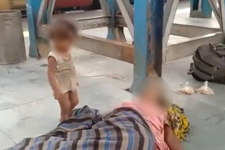 A toddler plays with the blanket covering his mothers body at Bihar railway station