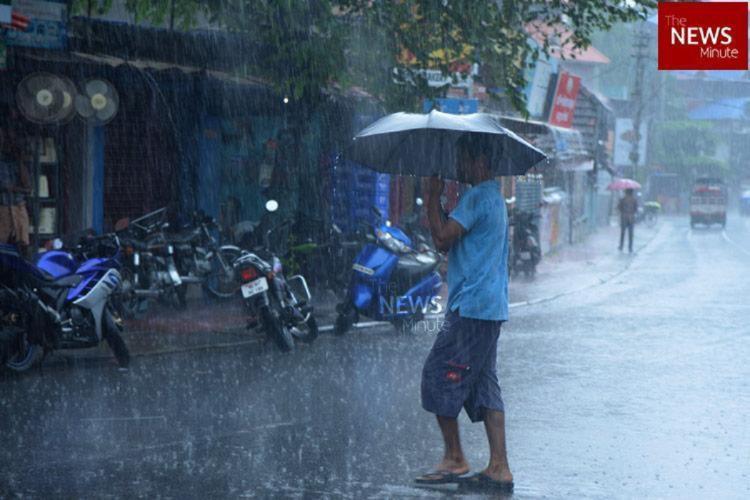 A man holding an umbrella and walking through Chennai rains