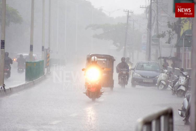 A bike rider flashes headlight while passing through a road during rain Few other vehicles are behind him