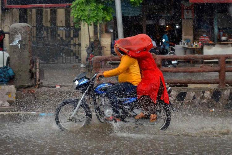Man riding a bike in rains while a woman pillion rider covers both with red dupatta