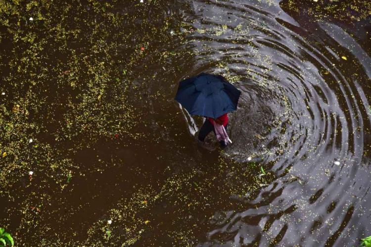 A man walking through a pool of water holding an umbrella