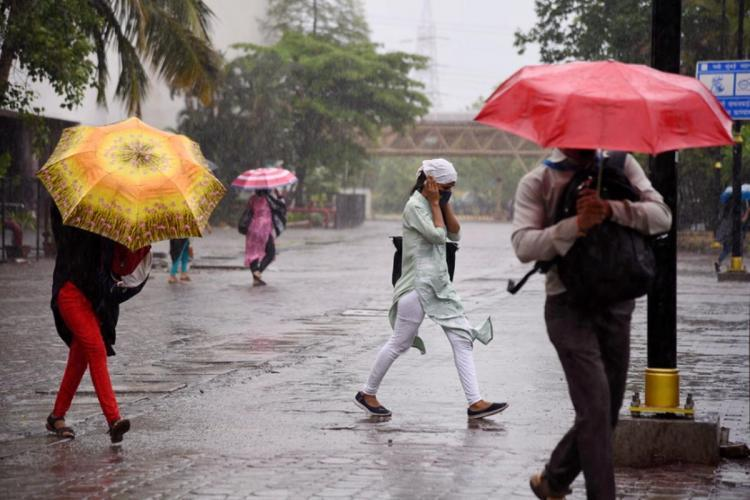 People shielding themselves from heavy rains with umbrellas as they walk towards their destination in different directions