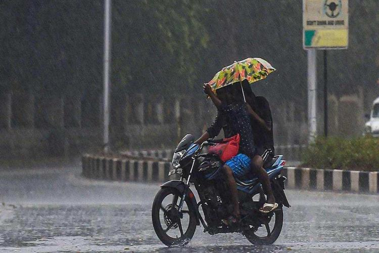 Two people on a motorcycle holding up a yellow umbrella to shield themselves from the rain