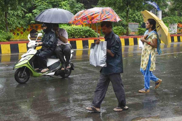 People crossing road, while two persons drive by on scooter amid rainfall