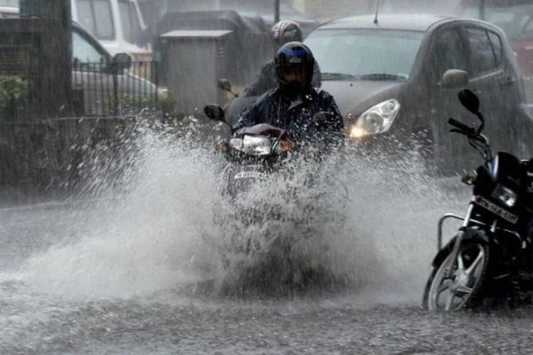 A bike crossing a flooded street on a rainy day in Chennai