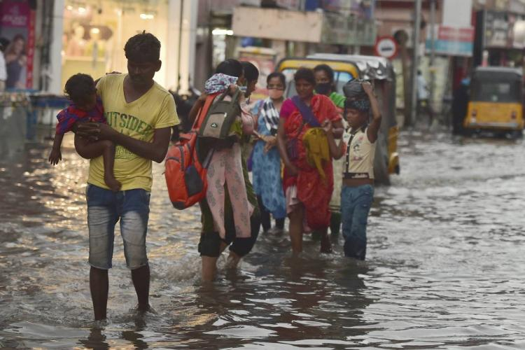People wading through a flooded street in Chennai