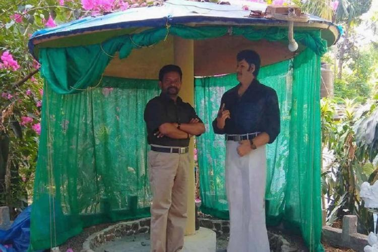 Rajan standing near a sculpture of late Malayalam actor Jayan that he sculpted Rajan is wearing khaki trousers and black shirt Jayans scultpure is seen in white bellbottom trousers and a dark blue shirt