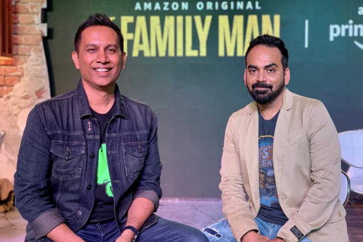 Producers Raj and DK are seen posing in the photo while the poster of The Family Man is seen in the background